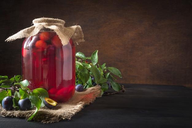 木の板に大きな瓶で自家製缶詰梅コンポート。素朴なスタイル。