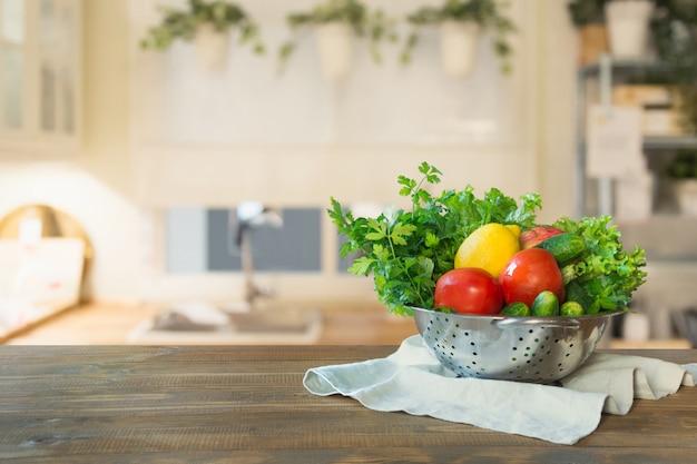 卓上に野菜とぼやけキッチン。設計のためのスペース。