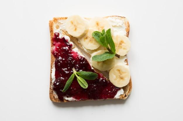 ベリージャム、バナナの入った、健康的で無糖の子供の朝食のサンドイッチ。