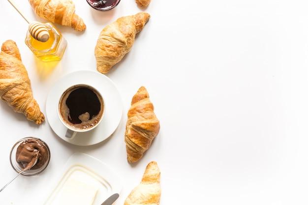 一杯のコーヒーと焼きたてのクロワッサン。上面図。コピースペース。