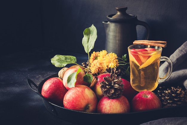 ブラックボードのビンテージトレイにレモン、スパイス、シナモンとアップルティー。秋の静物。閉じる。