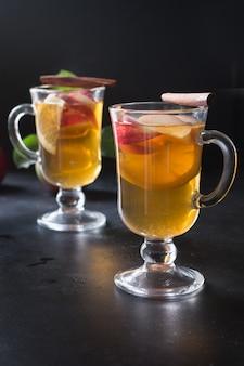 ブラックボードにレモン、スパイス、スライスされたリンゴ、シナモンとお茶のグラス。秋の静物。