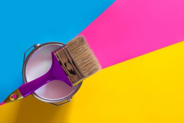 Фиолетовая кисть с открытой банкой белой краски,