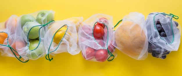 Фрукты и овощи в сетчатых мешках.