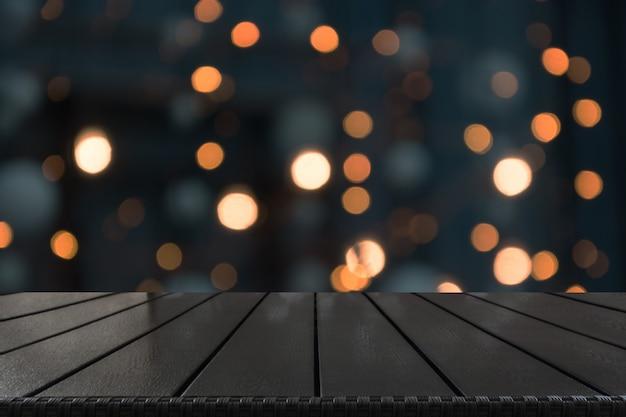 前景としてぼやけた金の花輪と木製卓上。クリスマス製品を表示するための背景。
