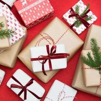 クリスマスギフトボックスは、装飾紙と赤い表面の装飾的な赤いロープリボンに包まれました。