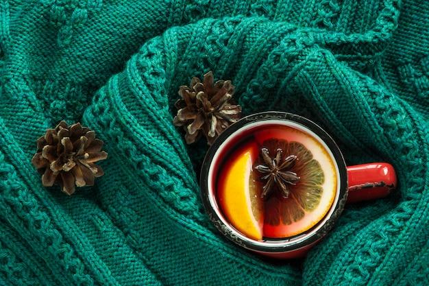 クリスマスと冬の伝統的な温かい飲み物。暖かい緑のスカンジナビアのセーターに包まれたスパイスの入った赤いマグカップのホットワイン。