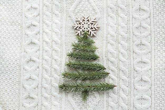 スプルース、モミの木、雪、白いニットの背景とのクリスマス。ホリデーカード。ビンテージ・スタイル。