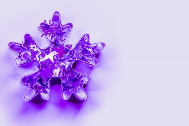 ネオンのピンクと青の光線の雪片としてクリスマスカッター。創造的なクリスマスのパターン。