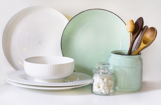 食器、食器、調理器具、その他の白いテーブルトップにある白とターコイズの異なるもの。