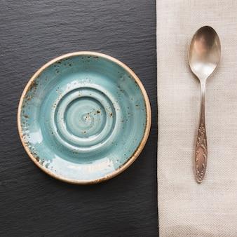 コピースペースを持つ黒いスレート皿に素朴なナプキン、スプーン、ブループレート