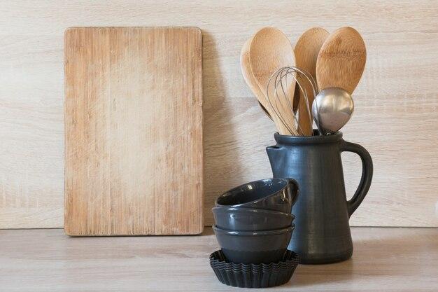 Посуда, глиняная посуда и разные вещи на деревянной столешнице.