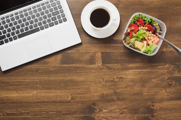 オフィス、サラダ、木製のテーブルの上のコーヒーで健康的なビジネスランチ。