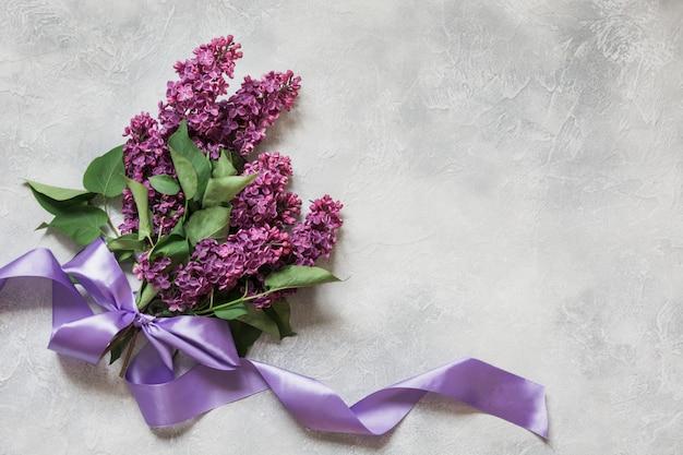 Букет из фиолетовой сирени на светлом столе в виде сверху