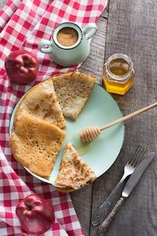 プレート上の蜂蜜とパンケーキのおいしい伝統的なロシアの朝食。素朴なスタイル。