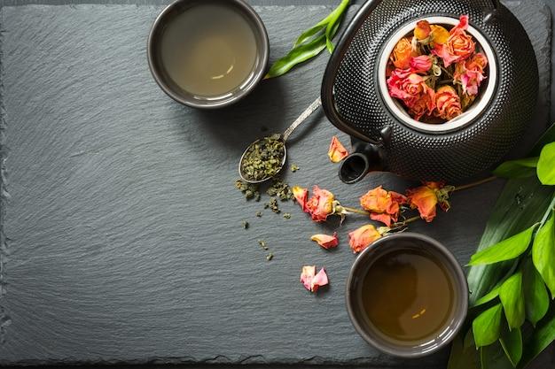 黒いスレートの乾燥したバラの花と緑茶