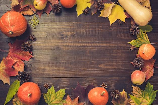 カラフルな葉と木の板にカボチャの秋と感謝祭の境界線。コピースペース。秋。黄金の秋。