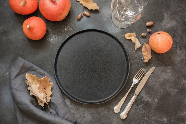 黒いテーブルの上のカボチャと感謝祭やハロウィーンの場所の設定。上面図。