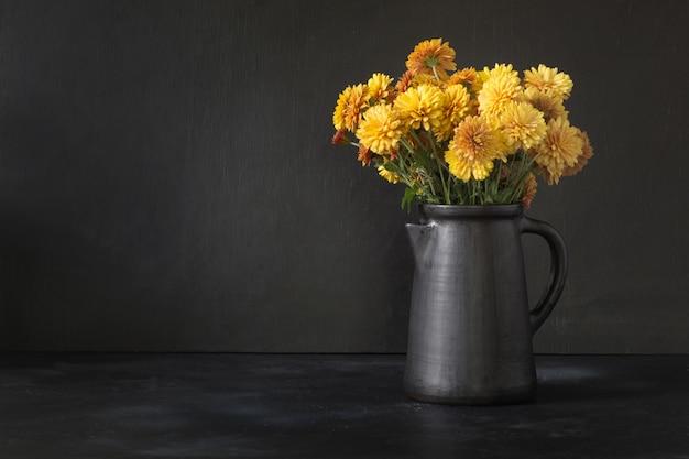 Осенний темный натюрморт. осень с желтыми цветами хризантемы в глиняной вазе на черном фоне.