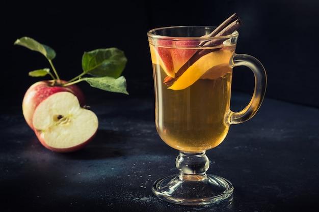 Стакан теплого яблочного чая с лимоном и корицей на черном столе. осень натюрморт.