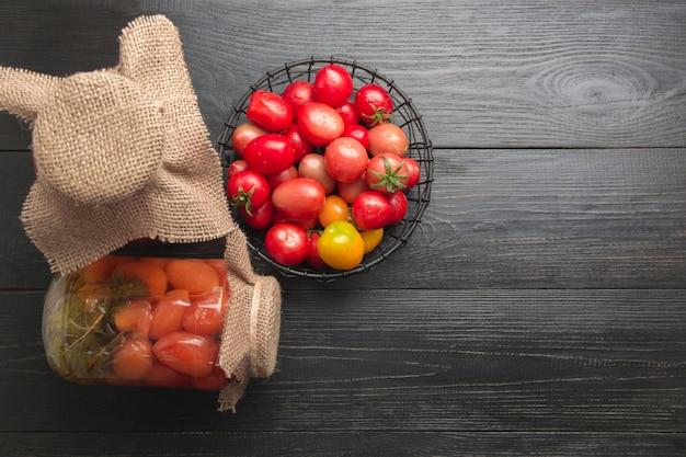 木製の暗いボード上のガラスの瓶に缶詰の野菜トマト上からの眺め自家製の収穫秋の準備。宿題と伝統。