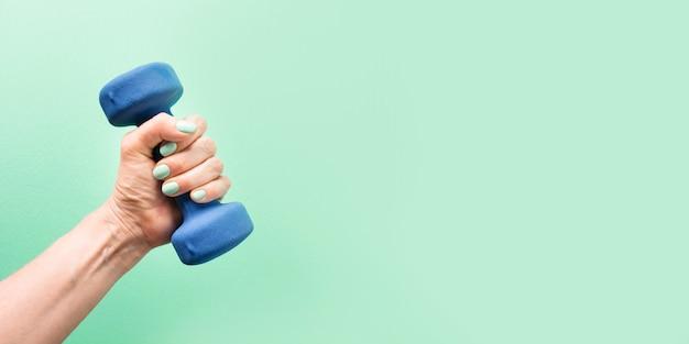 緑の背景スポーツフィットネス機器に青いダンベルを持つ女性の手