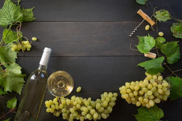 ワイングラス、木製のテーブルに熟したブドウの境界線と白ワインのボトル