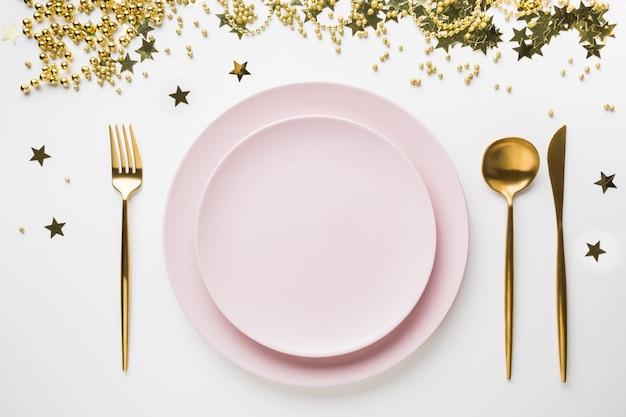白地にピンクの食器、黄金の銀器でクリスマステーブルの設定。上面図。