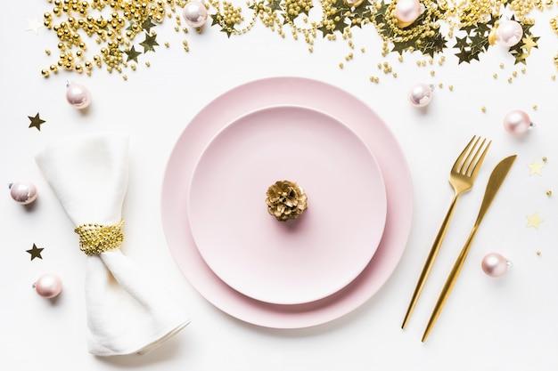 Сервировка стола рождество с розовой посудой, золотые серебро на белом. вид сверху.