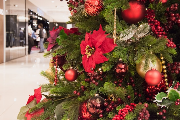 モールのインテリアで背景をぼかした写真のクリスマスツリー赤デザイナーボール。