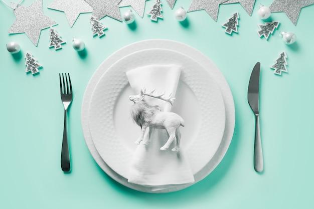 Сервировка стола рождество белая зима с оленями на фоне мяты нео