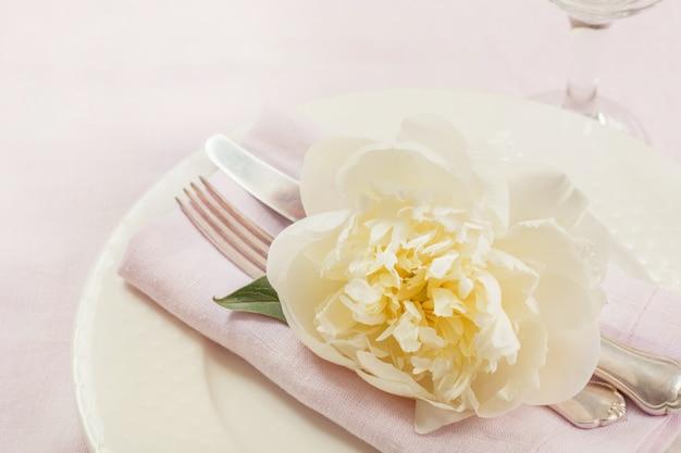 Сервировка стола элегантность с растением на розовой льняной скатерти