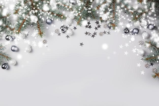 モミの枝ツリー、パステル調の明るい背景に銀のボールとクリスマス組成。メリークリスマスカード。冬休み。明けましておめでとうございます。