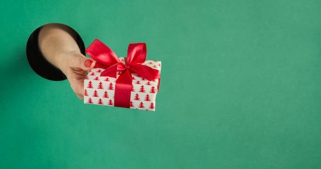 Женская рука держа коробку подарка рождества через круглое отверстие в зеленой книге.