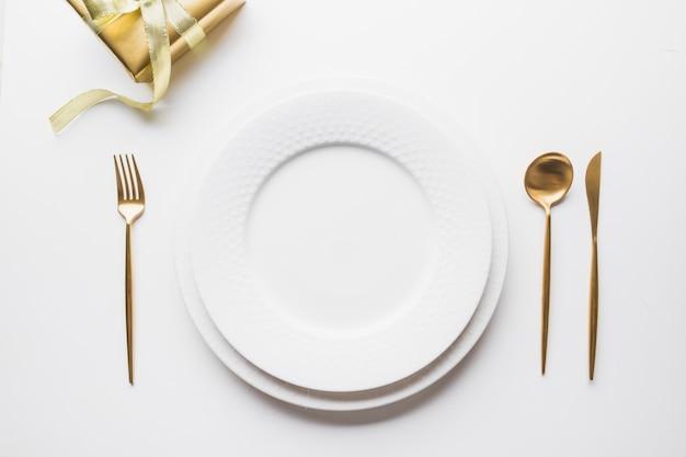 Элегантная сервировка стола с золотыми столовыми приборами