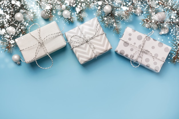 Рождественская композиция с еловыми ветками и белыми подарочными коробками