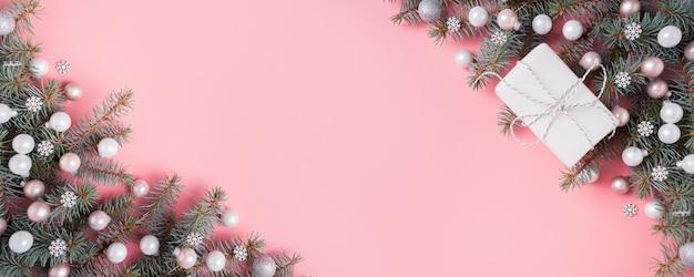 Рождественский серебряный розовый стеклянный шар и еловые ветки на розовом