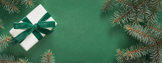 クリスマスツリーと緑のメリークリスマスカードに白いギフトとクリスマスの境界線。冬休み。明けましておめでとうございます。テキスト用のスペース