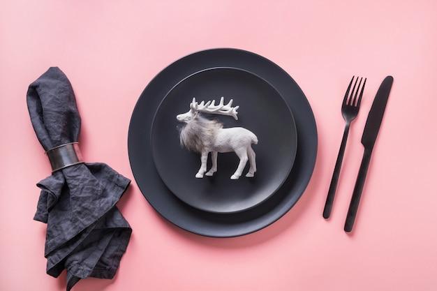 Сервировка стола рождества черная с северным оленем на розовой предпосылке. вид сверху.