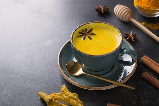 黒のクルクマパウダーとアニススターアーユルヴェーダゴールデンウコンラテミルクのカップ。閉じる。