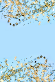 青に金色のキラキラ紙吹雪星とクリスマスフレーム。フラット横たわっていた。上からの眺め。クリスマスの垂直方向の境界線。