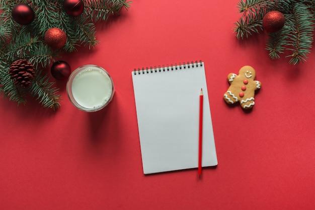 クリスマスミルク、クッキー、赤のジンジャーブレッドとサンタクロースの空の空白の手紙。上面図
