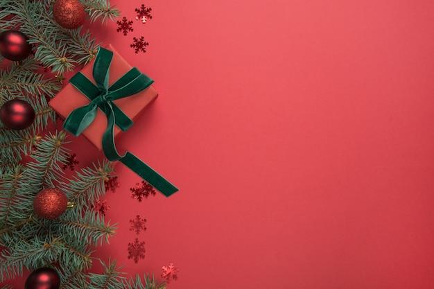 モミの木と赤い背景のギフトクリスマスの境界線。グリーティングカード。