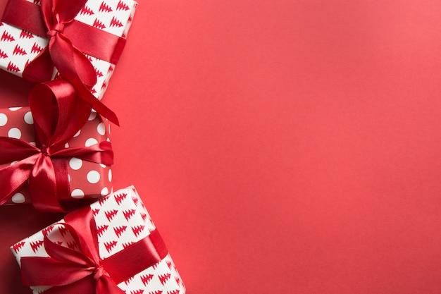赤の背景にクリスマスプレゼントのクリスマスの境界線。ボクシングデー。グリーティングカード。