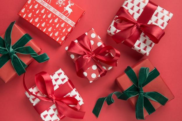 赤の背景にクリスマスプレゼントのクリスマスのパターン。ボクシングデー。グリーティングカード。冬。明けましておめでとうございます。