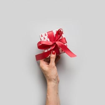 赤の弓とクリスマスの手作りギフトボックスを持つ女性の手。正方形の画像。グリーティングクリスマスカード。ボクシングデー。