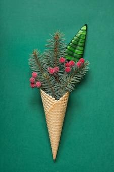 Конфета рождества, красные шарики в конусе мороженого на зеленом цвете. рождественская праздничная открытка. вид сверху.