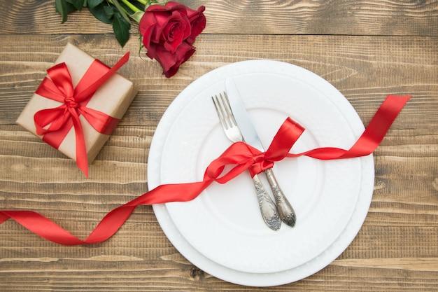 ロマンチックなディナー。木製のバレンタインデーのお祝いテーブルの設定。赤いバラとロマンチックなギフト。上面図。