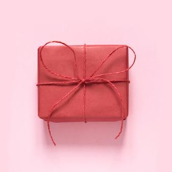 Валентинка. красный подарок с бантом веревки на пастельный розовый. вид сверху.