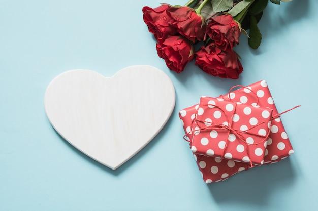 Поздравительная открытка дня валентинки с букетом красных роз и подарка, сердца как пробела для текста на голубой поверхности. копировать пространство